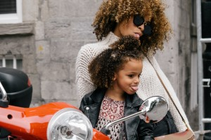 woman making faces with little girl in motorcycle mirror