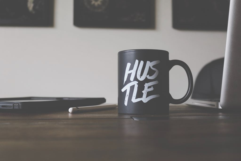 Side Hustle: Picture of a coffee mug that says Hustle
