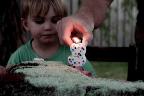 lighting candles on the dinosaur cake