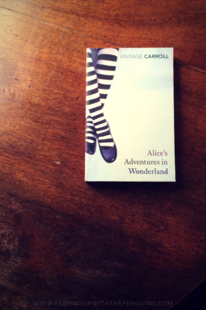 Alice's Adventures in Wonderland - Lewis Carroll - book laid on a wooden table - Keeping Up With The Penguins