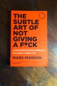 The Subtle Art Of Not Giving A Fuck - Mark Manson - Book Laid on Wooden Table - Keeping Up With The Penguins
