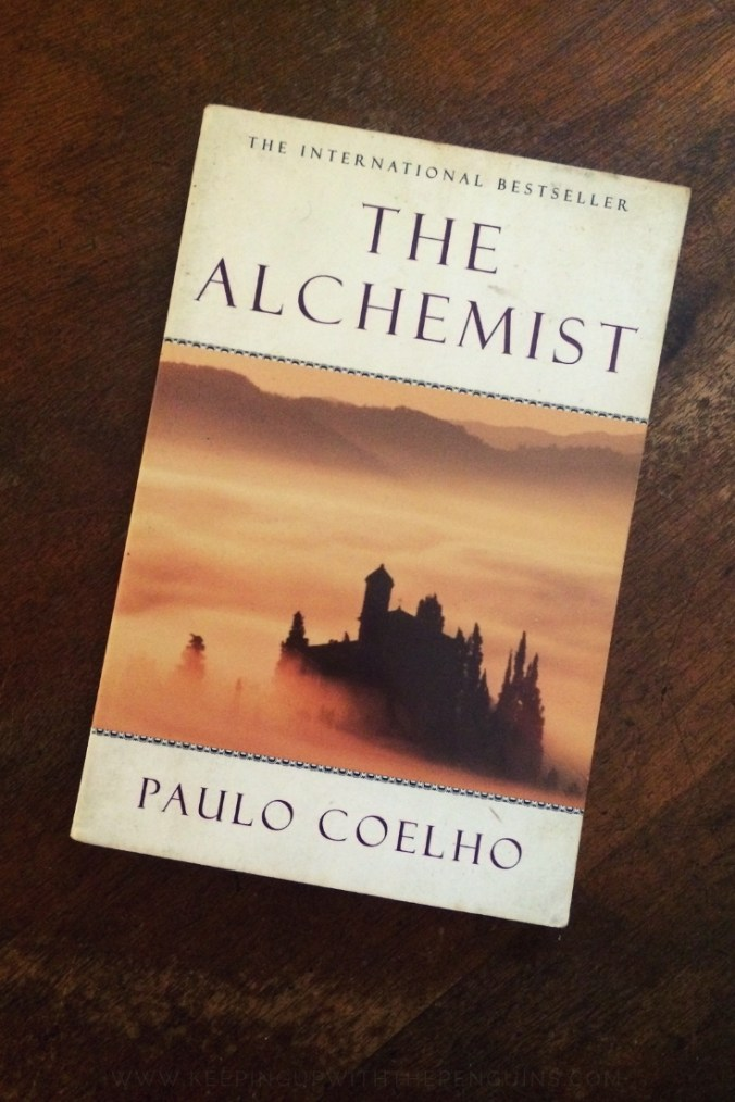 The Alchemist - Paulo Coelho - Book Laid on Wooden Table - Keeping Up With The Penguins