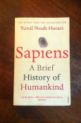 Sapiens A Brief History of Humankind - Yuval Noah Harari - Book Laid on Wooden Table - Keeping Up With The Penguins