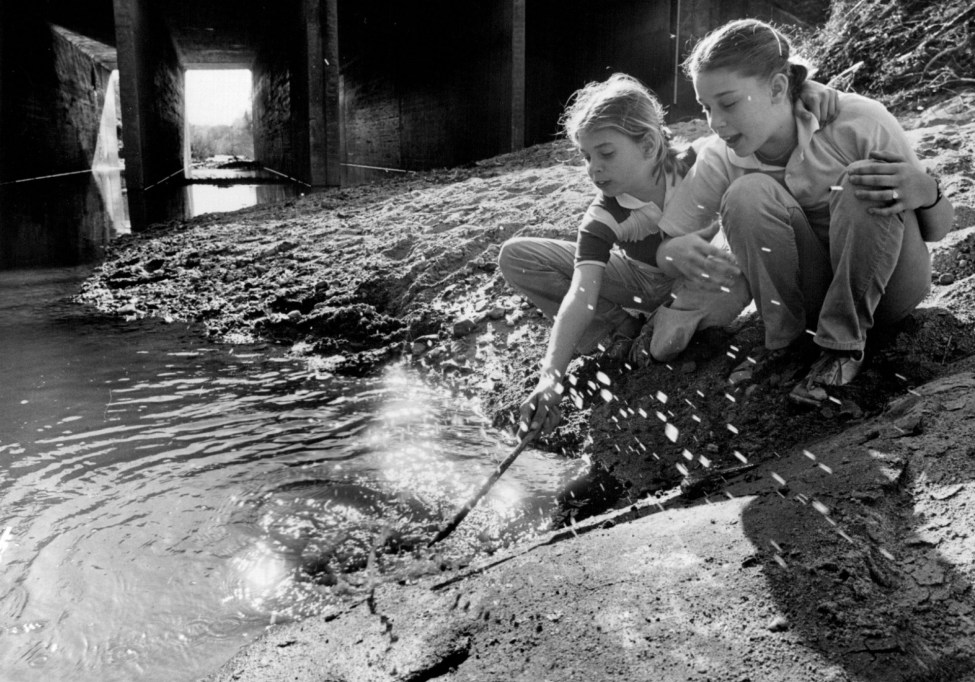 In April 1980, Mary Reynolds and Jennifer Reid, both 11, landed a crayfish from Briar Creek under Providence Road. Photo: Charlotte Observer archives
