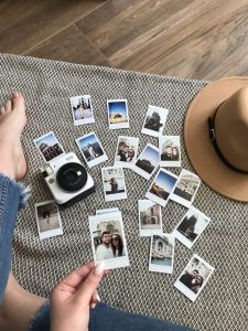 woman looking at a pile pf photos with a hat and camera by her feet