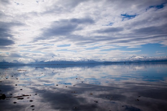 The glassy calm water reflects the gorgeous clouds and mountains.