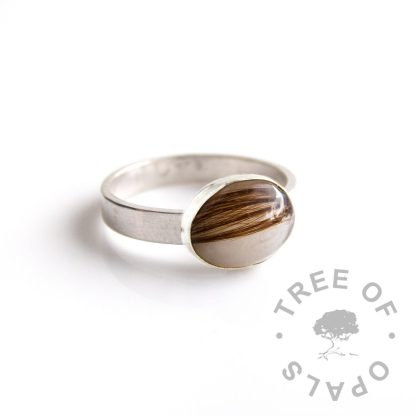 oval cabochon with hair and breastmilk set in a rubover bezel on a ring band