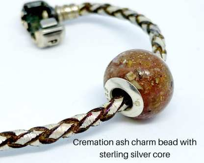 Large charm bead with cremation ashes and large charm bead inserts, shown on a leather Pandora bracelet. Image courtesy of Silver Keepsake Company