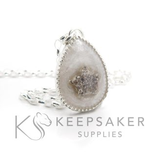 Cremation ashes teardrop necklace with unicorn white sparkle mix, ashes in a star shape. Classic chain, scalloped setting