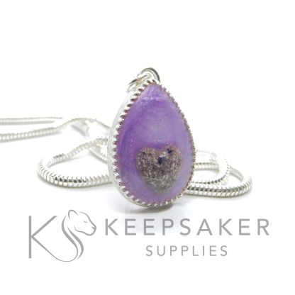 Cremation ashes teardrop necklace with purple sparkle mix, ashes in a heart shape. Snake chain, scalloped setting