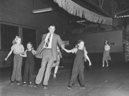bernard-hoffman-dad-in-business-suit-holding-hands-with-his-daughters-roller-skating-with-them-at-roller-rink