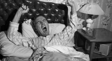 1950s yawning stretching man waking up in bed with tufted leather headboard