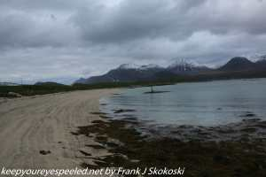 clouds and snow capped mountains along beach