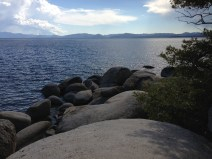 Lake Tahoe with rocks in foreground and blue sky with clouds above