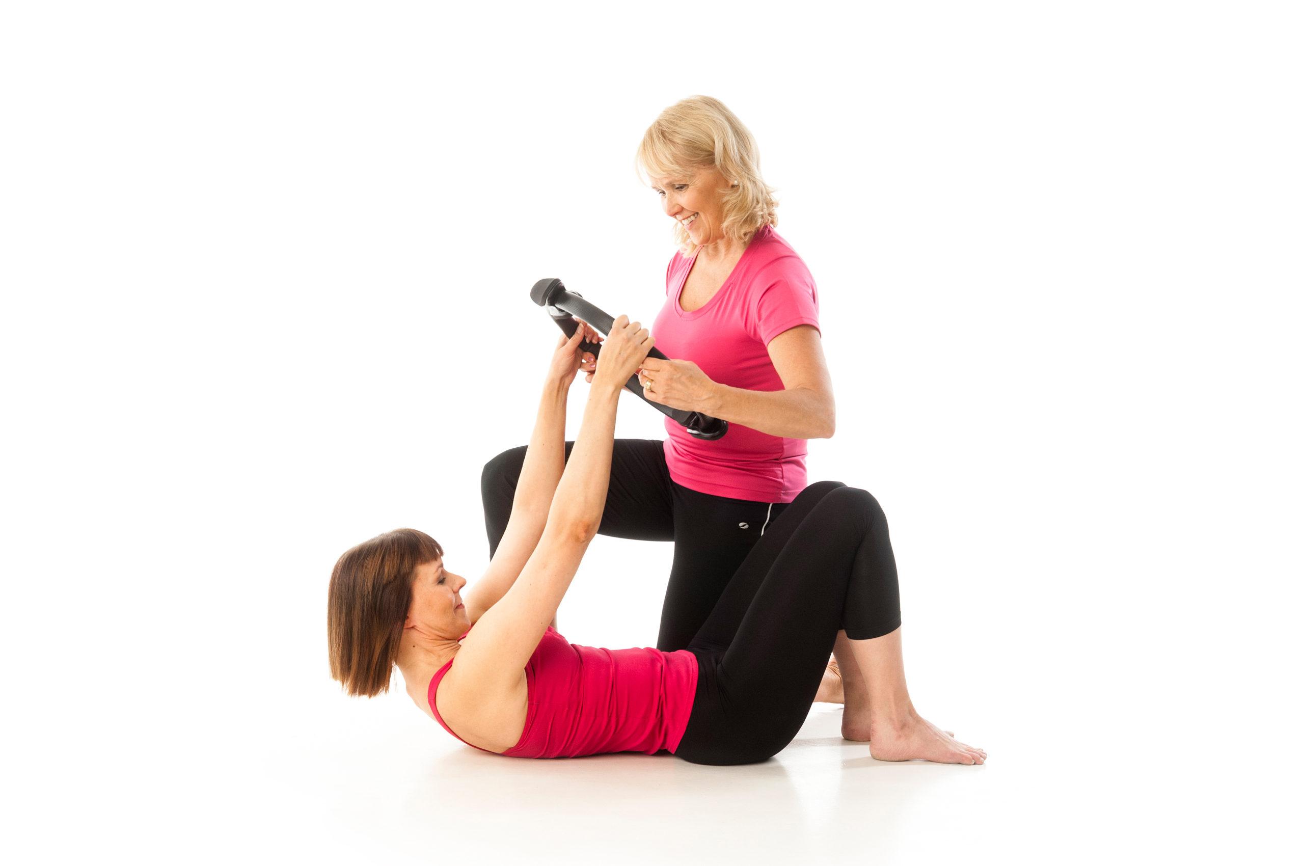 Toinen nainen koukkuselinmakuulla toinen nainen ohjaa Pilates-renkaalla