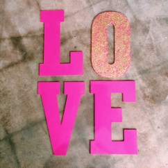 Got crafty with some large MDF letters from Hobby Lobby, hot pink acrylic paint, and gold glitter for an eye-catching Valentine's window display.