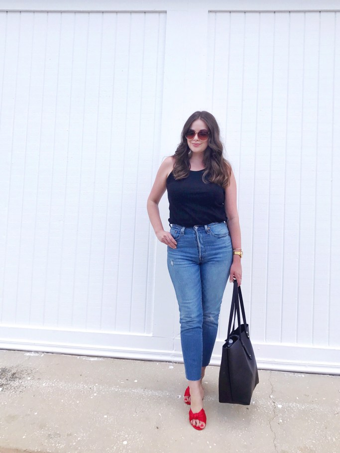 Style blogger wearing a casual summer outfit with a black tank top, Levi's 501 skinny jeans, red satin slide sandals and a large black leather tote bag.