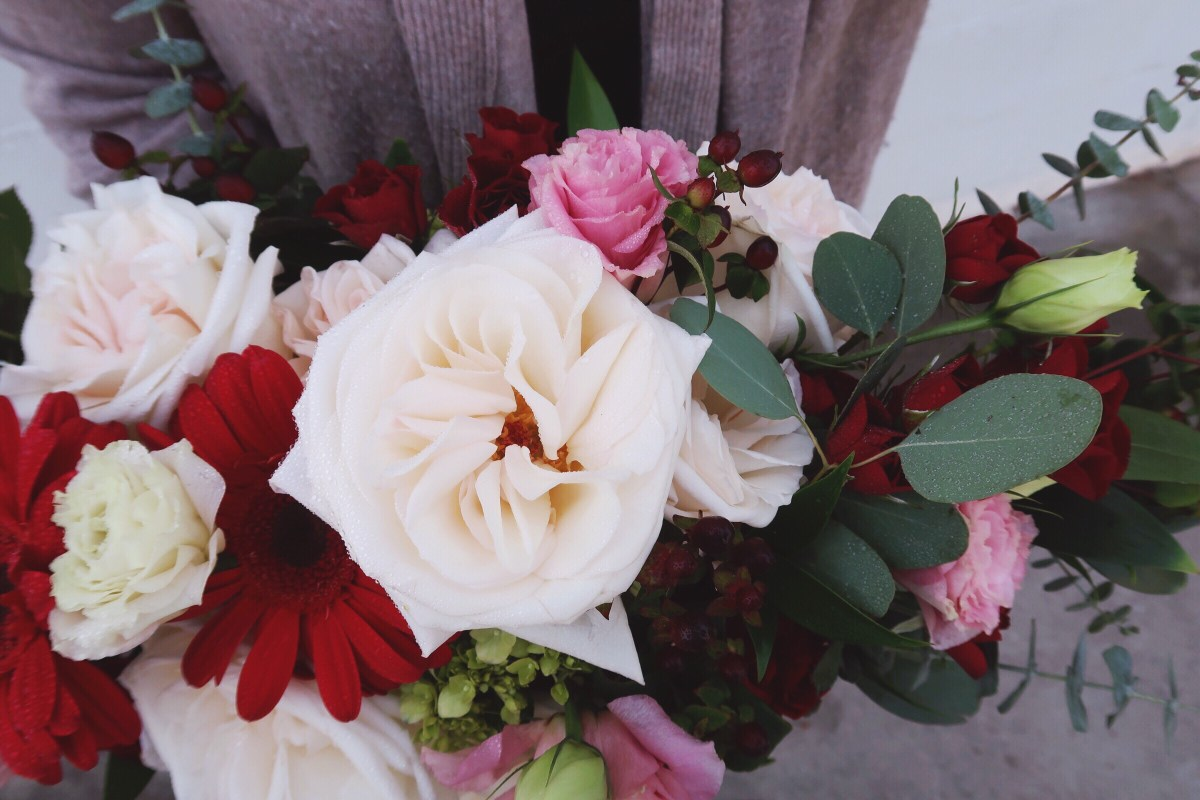 Fresh floral bouquet with open blush garden roses, pink lisianthis, red gerbera daisies and assorted eucalyptus.