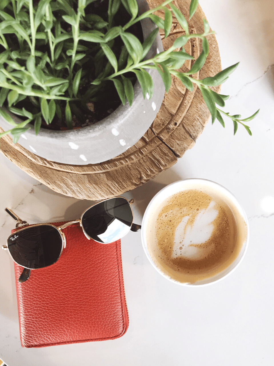 Coffee shop flat lay with Ray-Ban hexagonal sunglasses, Cuyana small zip around wallet, and cappuccino