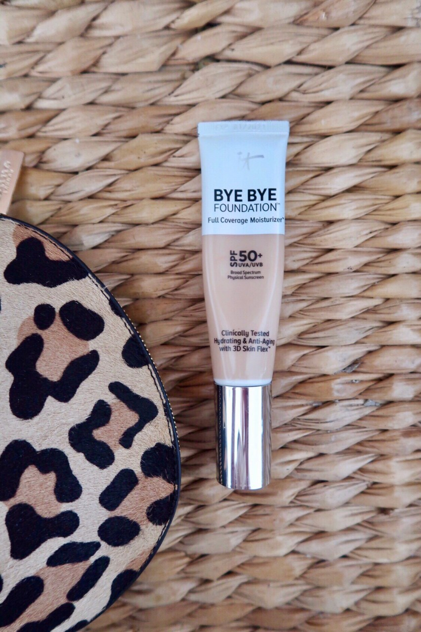 It Cosmetics Bye Bye Foundation Full Coverage Moisturizer SOF 50+ next to a leopard print makeup bag.