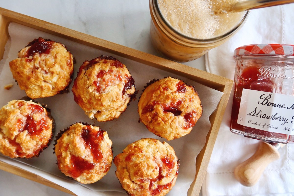 Diane Morrisey's 'Jammy Muffins' on a wood try beside a jar of Bonne Maman strawberry preserves and a mason jar of iced coffee.