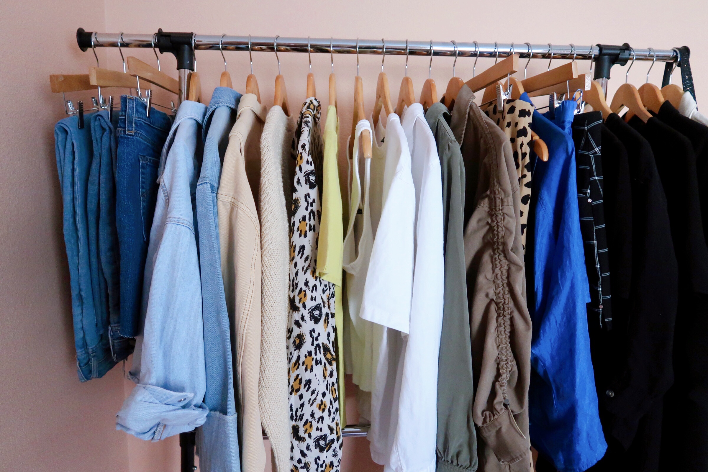 summer capsule wardrobe hanging on a rolling rack and organized by color