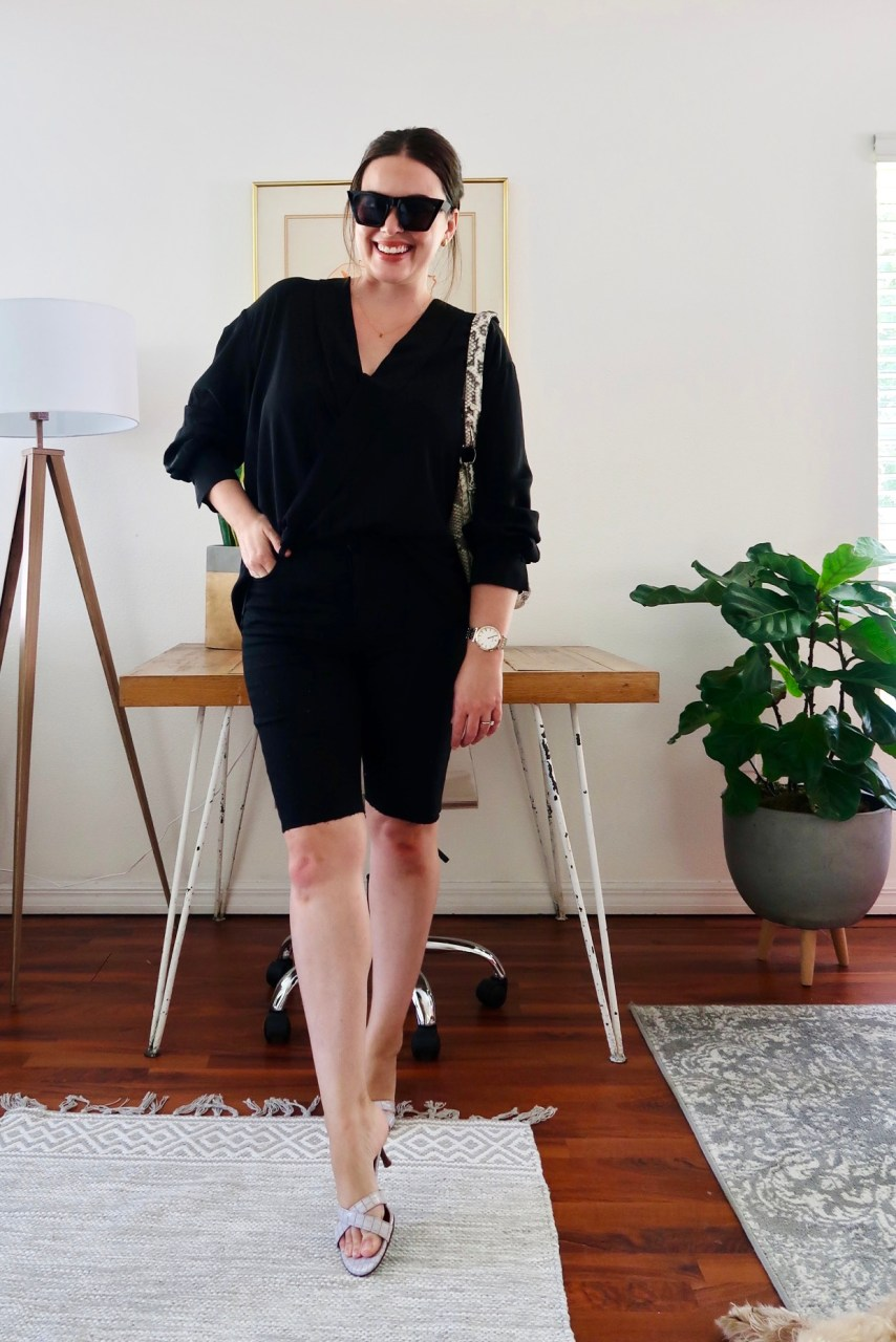 Style blogger wearing casual black summer outfit with silk top and bermuda shorts