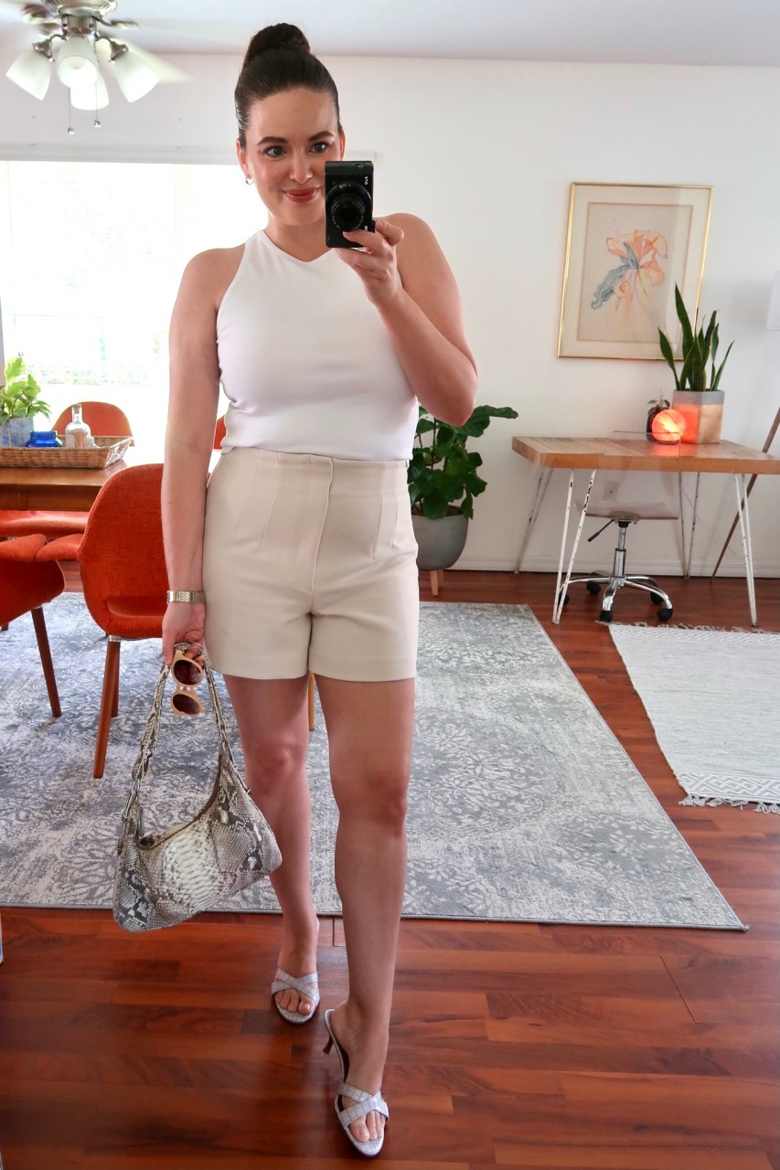 Style blogger wearing light neutral summer outfit of Zara high waisted shorts with a white tank and lavender sandals