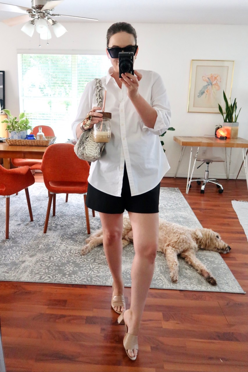 Style blogger wearing a casual minimal outfit of black Zara high waisted shorts, white button down shirt, and nude leather Calvin Klein Noelly mule sandals.