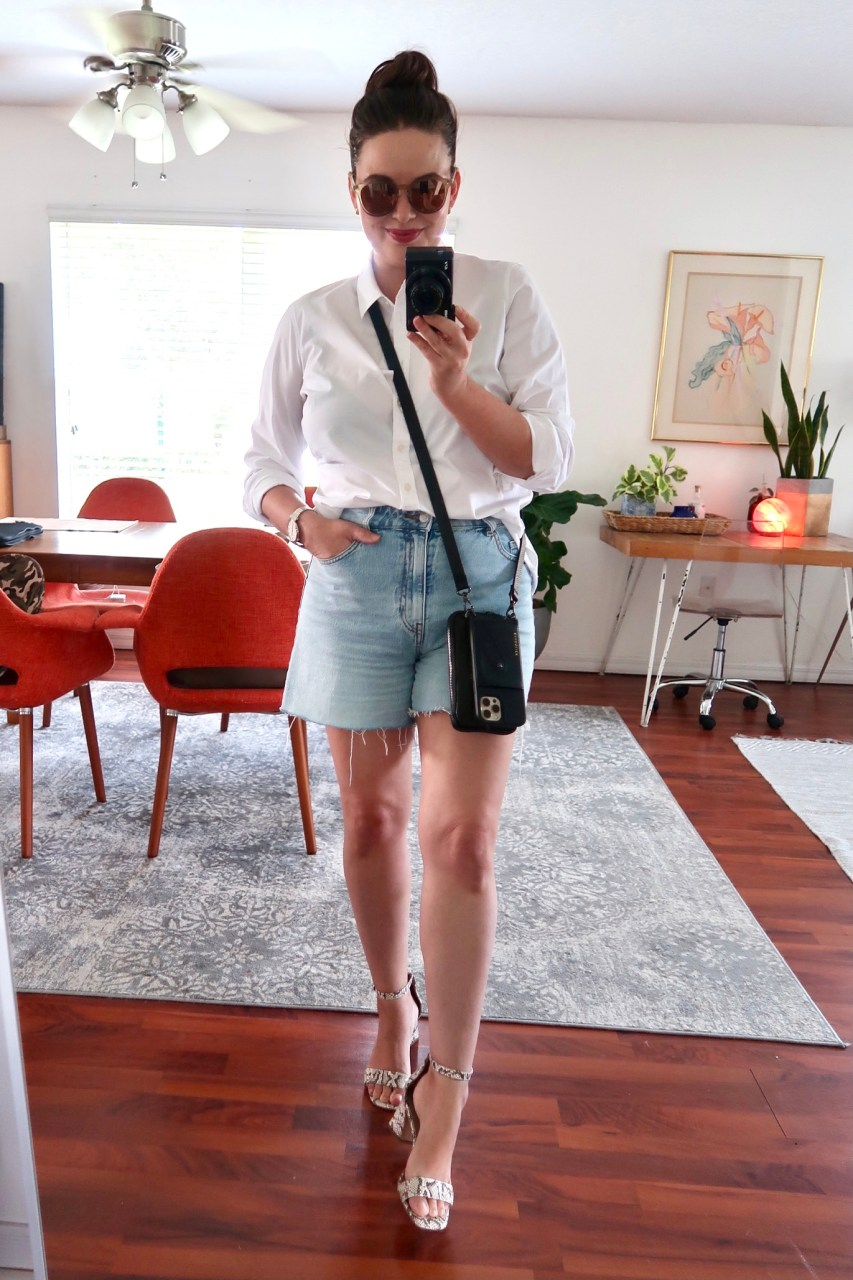 Style blogger wearing H&M high rise denim shorts with a classic white button down and Bandolier iphone crossbody