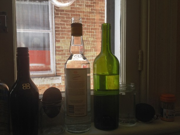 Wine bottles full of spare water for little tasks & needs in the kitchen window