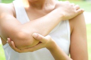 woman holding her elbow suffering from tennis elbow