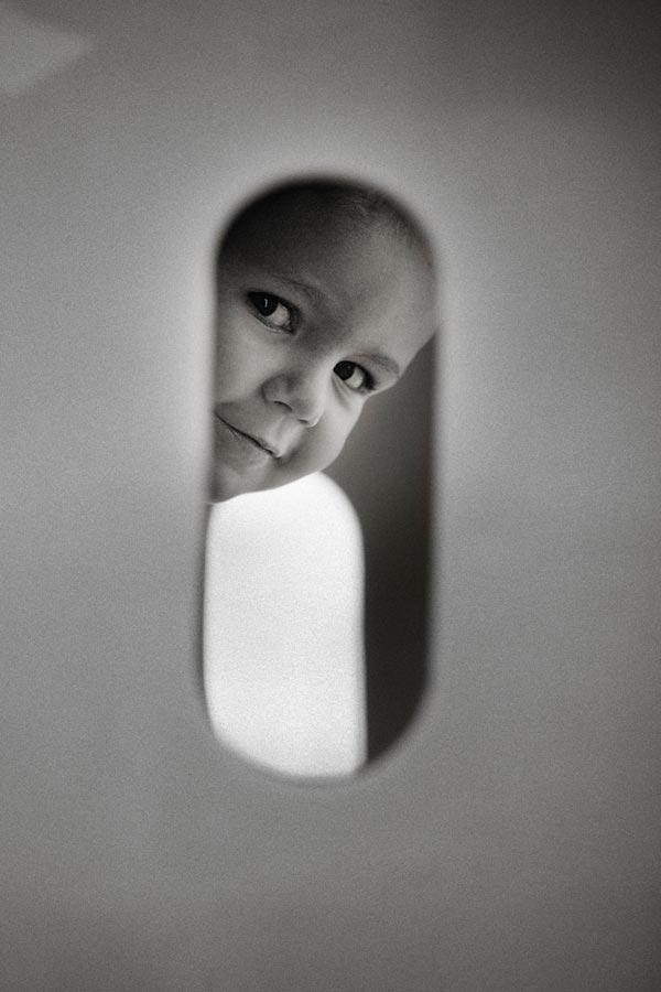 little boy looking trough hole