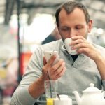 stock-footage-man-texting-on-smartphone-and-drinking-tea-in-cafe