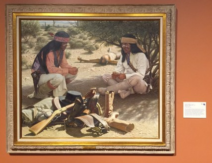 David Nordahl, 'Winner takes all', 1984, oil on canvas, at Booth Western Art Museum, Cartersville, GA. Photo credit Kelise Franclemont. The card reads: 'The calm manner of these Apache Indians playing cards contrasts with the troubling vision in the mind of their prisoner whose fate is in doubt. His gear goes to the winner, but to the captive, worldly possessions are now insignificant. Nordahl has made it his life's work to paint the everyday life and customs of the various Apache tribes.'