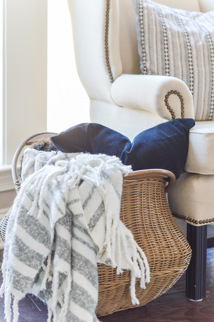 11 Ways to Use Baskets for Storage and Decor in Your Home   Kelley Nan Blanket and pillow basket next to chair