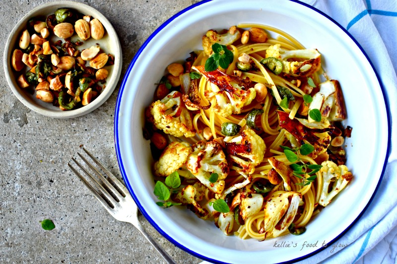 Cauliflower roasted in a surprising easy marinade and topped with pan-fried almonds, green olives and chilli flakes makes for a simple, vegan and healthy midweek pasta supper for 2.