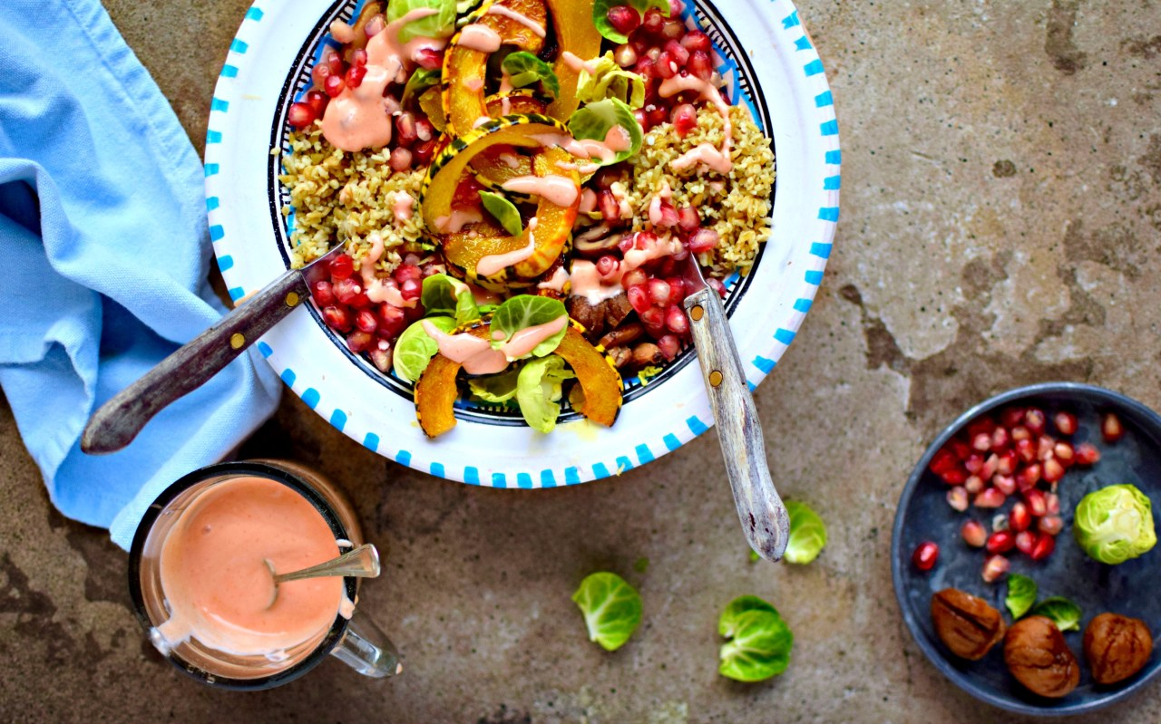 An A/W warm salad using winter squash, shredded sprouts, hearty grains, juicy pomegranate, earthy chestnuts, all topped off with a zingy vegan Buffalo ranch dressing to chase away the winter blues.