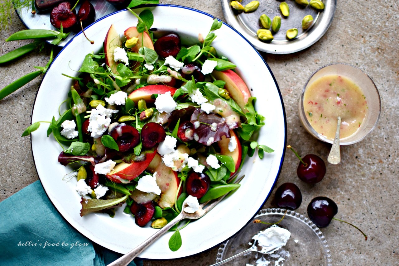 A simple lunch salad recipe highlighting seasonal cherries and peaches along with pistachios, sugar snap peas and a really rather special fat-free and fruity dressing. Add crumbles of goat's cheese or cashew ricotta for a yummy, creamy tang.