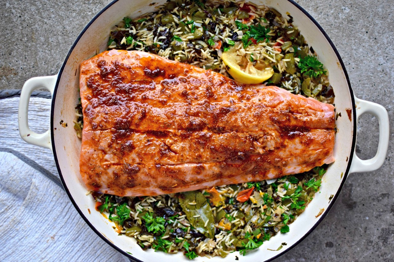 """Pearly-pink salmon kept juicywith a coating of creole spices and olive oil, cooked over vegetable-filled """"dirty"""" brown rice. A healthy, family-friendly and surprisingly quick and easy recipe for a midweek dinner. Leftovers are great cold in a wrap - lettuce or grain."""