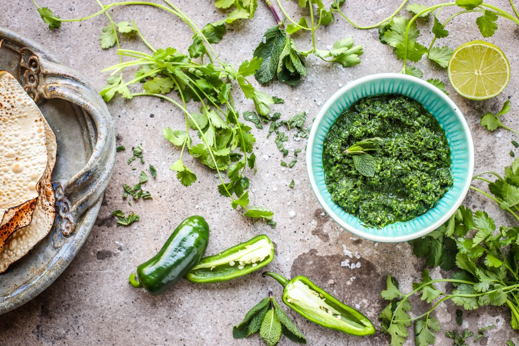 offset view of green herb chutney in small aqua bowl amidst fresh coriander, mint, limes, chillies, salt.