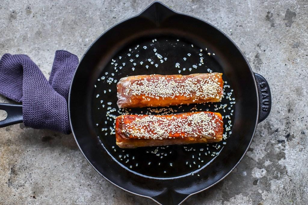 crispy Korean rice paper salmon in cast iron pan on concrete background