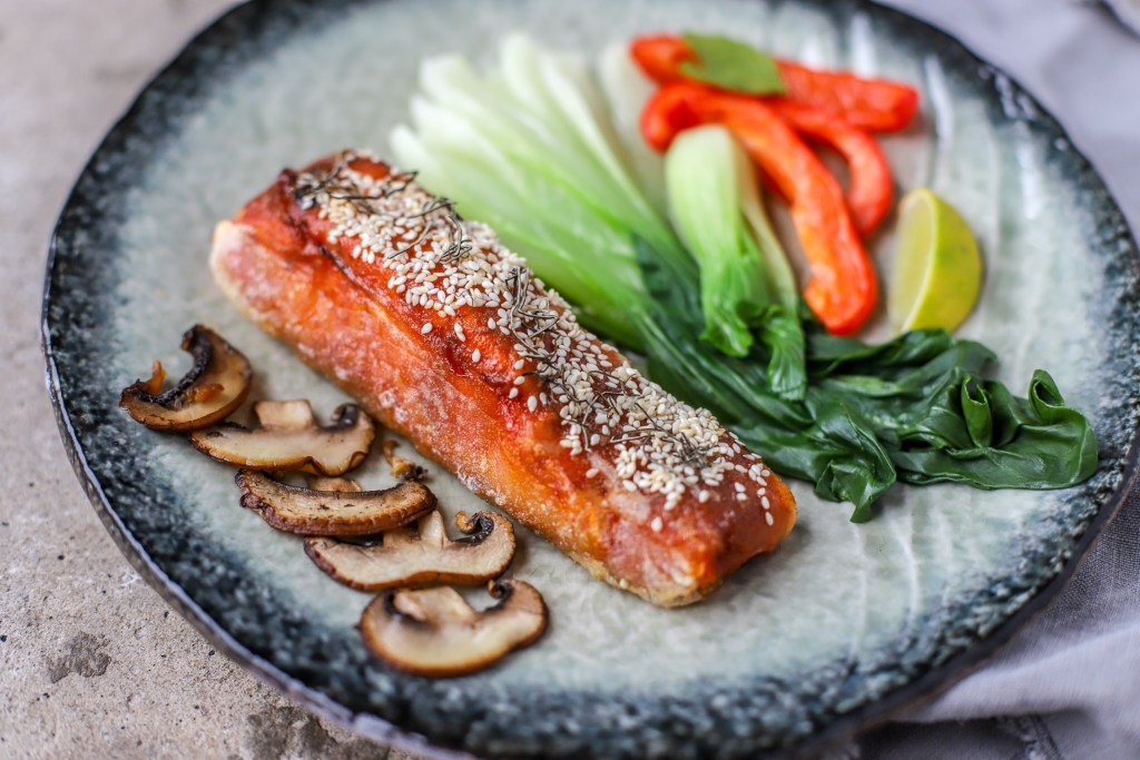 Korean salmon on plate with vegetables as side view