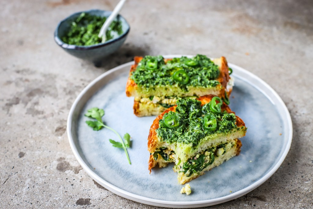 palak paneer toastie covered in coriander-mint chutney on pale blue plate