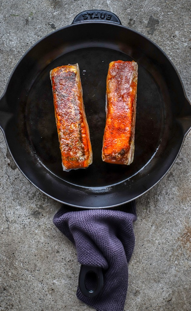 crispy Korean rice paper salmon in cast iron pan on concrete background