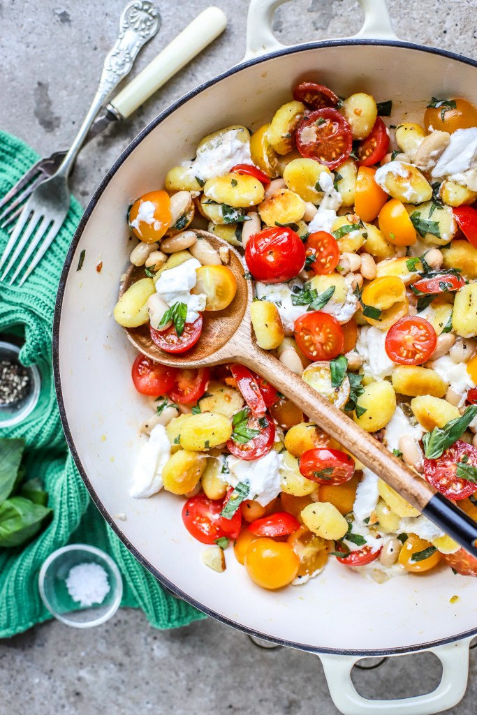 vertical view of white skillet containing cheesy gnocchi caprese with green cloth, vintage forks, salt and pepper on concrete background