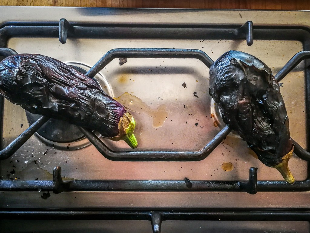 eggplants roasting over gas flame