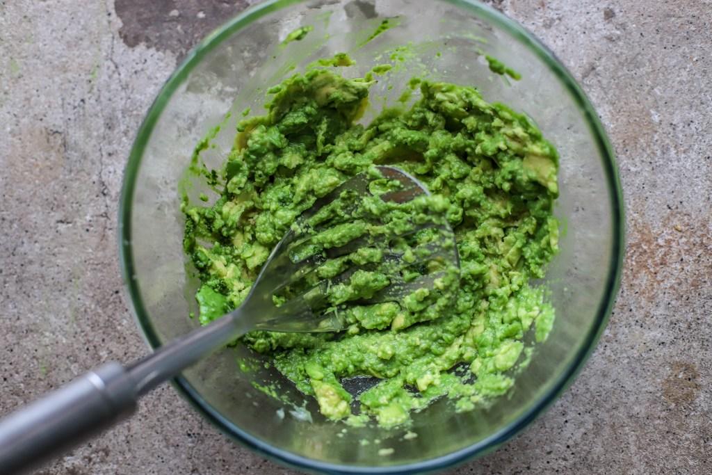 mashing avocados in a glass bowl