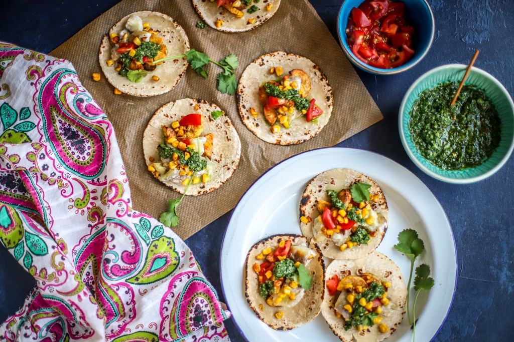 enamel plate and baking paper topped with vegetable soft tacos with colourful printed cloth