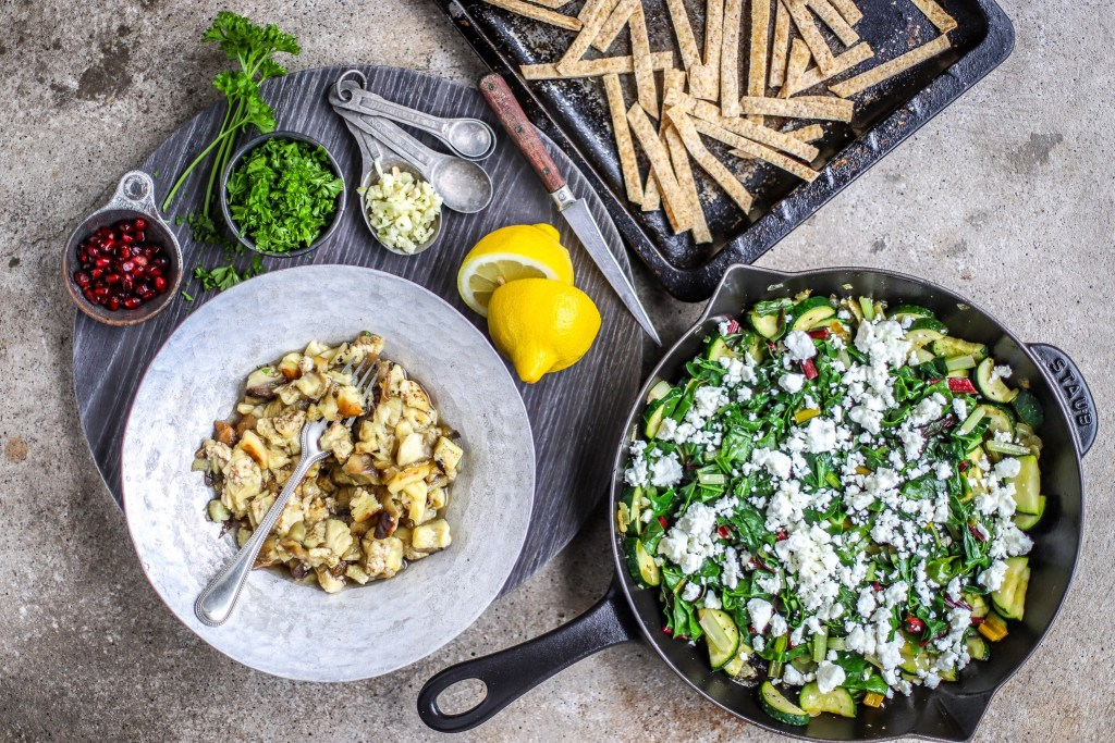 vegetables in skillet alongside bowl of eggplant dip and pitta breads toasts